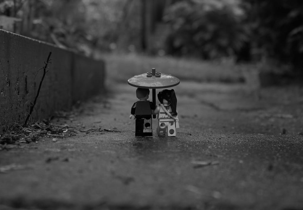 zwei Minifiguren unter einem Regenschirm