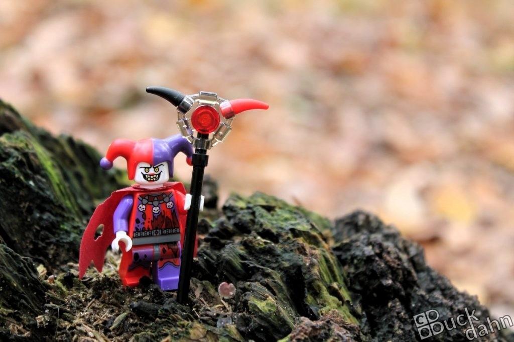 Jester-Minifigur auf einem bemoosten Baumstumpf im Wald