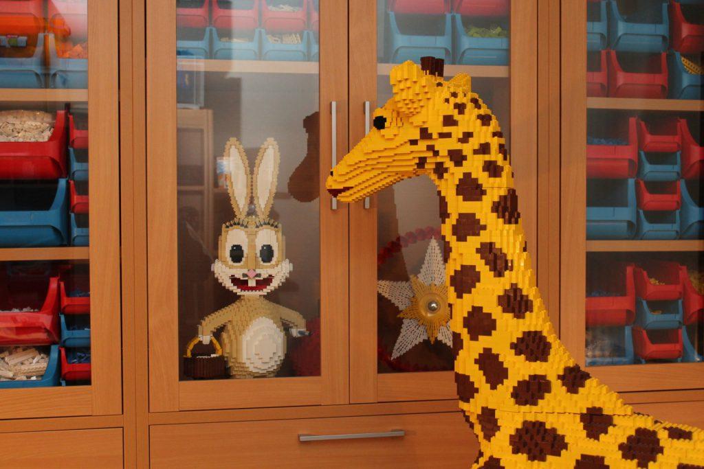 Hasenskulptur und sortierte Legoschachteln in einer Schrankwand, vor der die Giraffenskulptur steht
